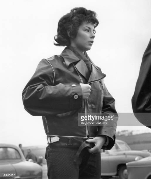 A young woman biker zipping up her leather jacket
