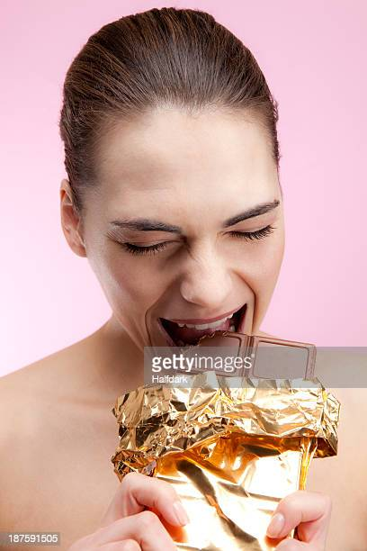 A young woman biting aggressively into a large chocolate bar