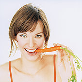Young woman biting carrot, smiling, portrait, close-up