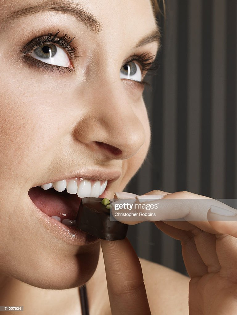 Young woman biting chocolate candy, looking up, close-up : Stock Photo