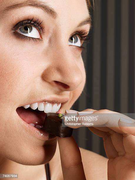 Young woman biting chocolate candy, looking up, close-up