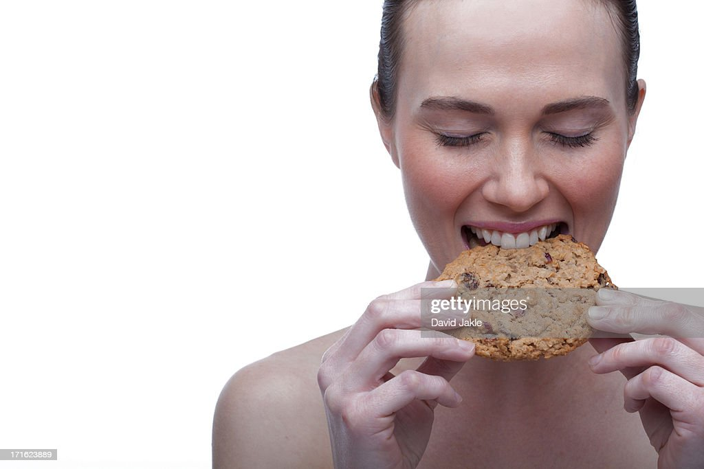 Young woman biting cookie : Stock Photo