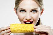 Young woman biting corn cob