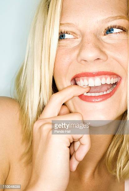 Young woman biting finger and smiling