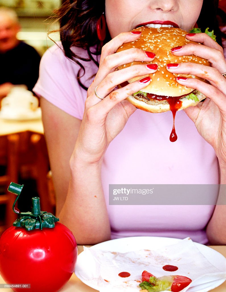 Young woman biting into hamburger in diner : Stock Photo
