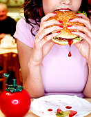 Young woman biting into hamburger in diner