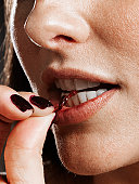 Young woman biting knotted cherry stem, close-up of mouth and fingers