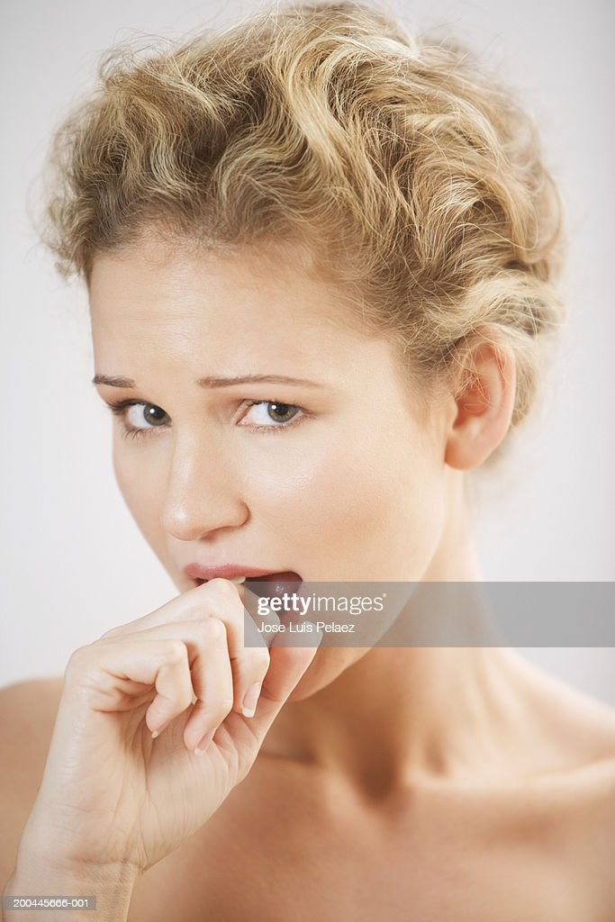 Young woman biting knuckle, portrait, close-up : Stock Photo