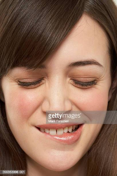 Young woman biting lip, close-up