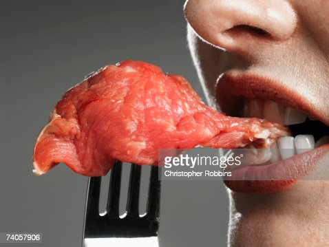 Young woman biting raw meat on fork, close-up of mouth : Bildbanksbilder