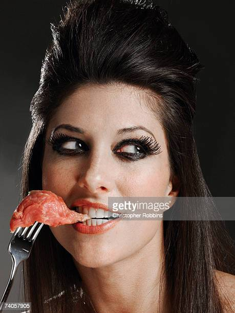 Young woman biting raw meat on fork, looking away, smiling, close-up