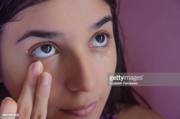 Young woman blending concealer under her eyes.
