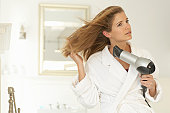 Young woman blowdrying hair, wearing dressing gown