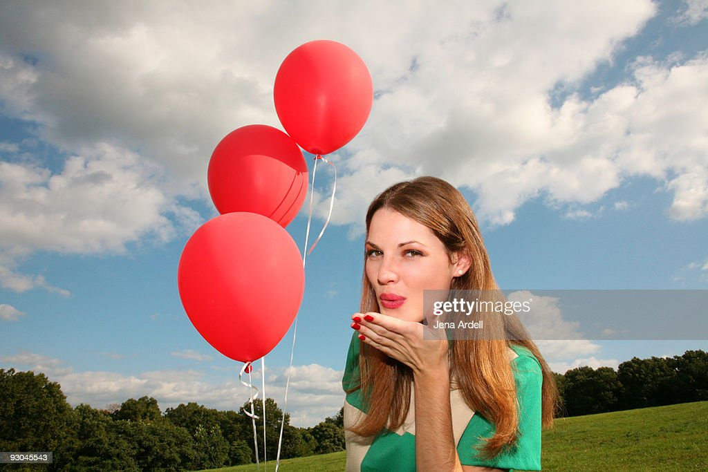 Young woman blowing a kiss & holding red balloons : Stock Photo