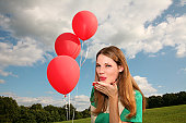 Young woman blowing a kiss & holding red balloons