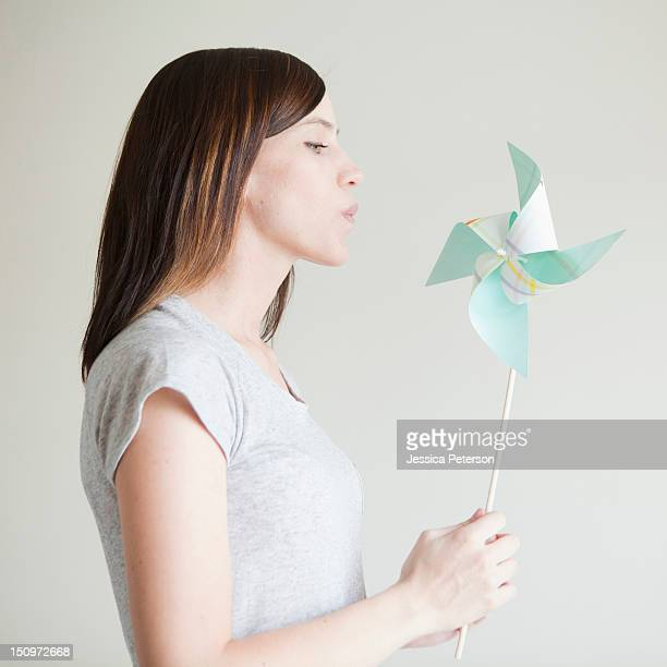Young woman blowing at paper fan