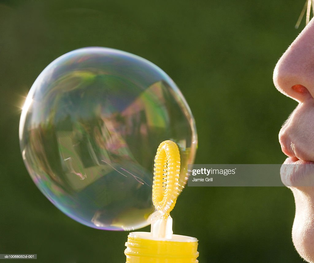 Young woman blowing bubble, close up, side view : Stock Photo