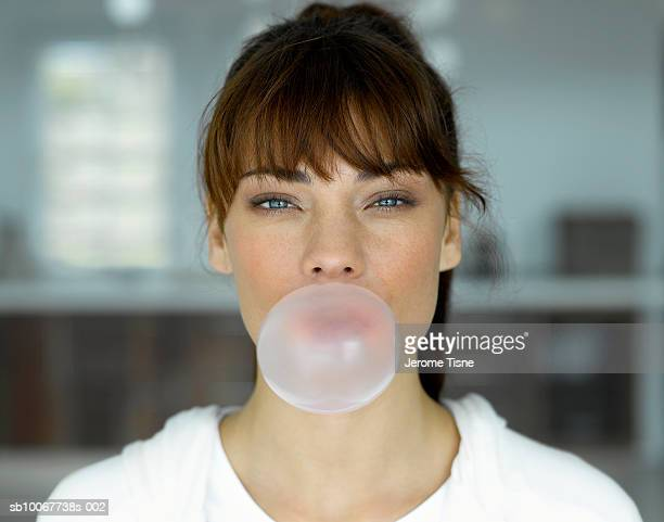 Young woman blowing bubble, indoors, portrait
