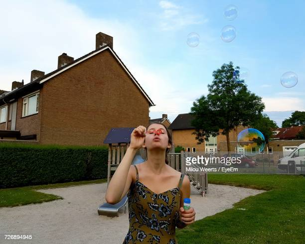 Young Woman Blowing Bubbles At Playground In Town