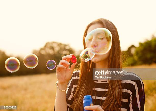 Young woman blowing bubbles in field.