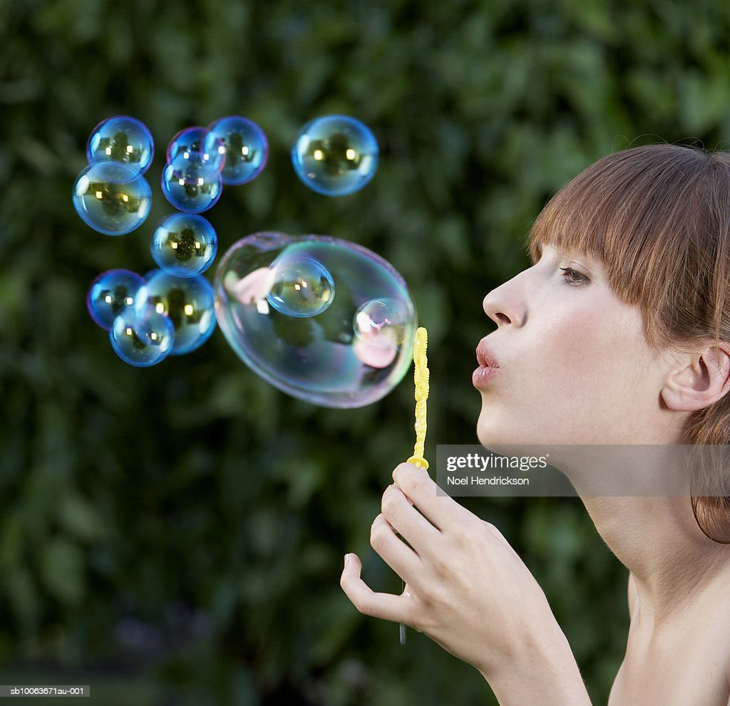 Young woman blowing bubbles outdoors, side view : Stock Photo