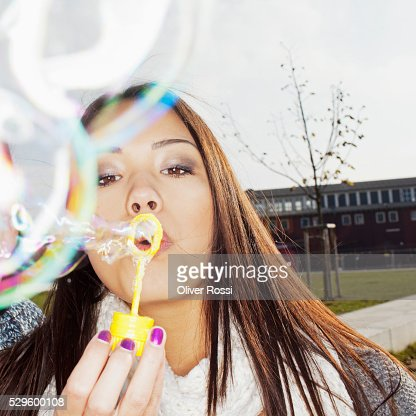 Young woman blowing bubbles : Photo