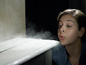 Young woman blowing dust off shelf