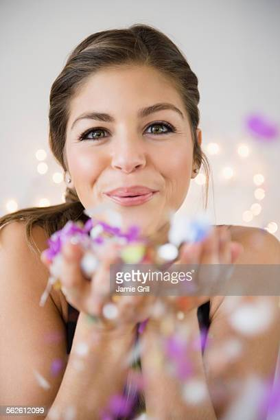 Young woman blowing flower petals