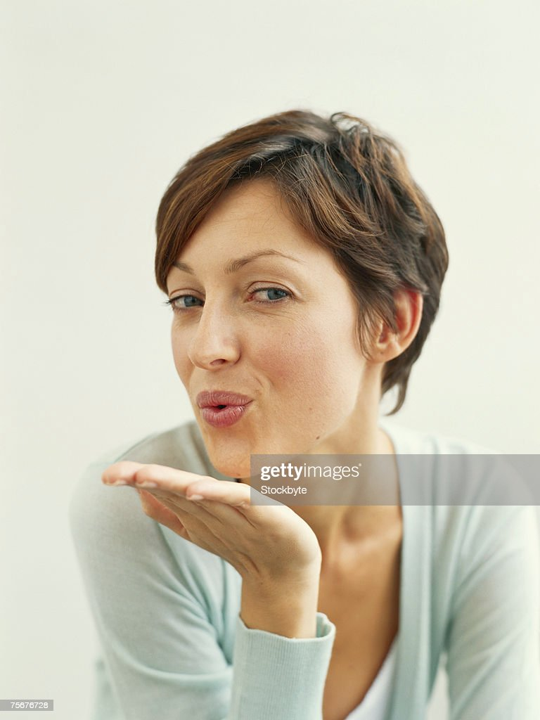 Young woman blowing kiss, portrait, close-up