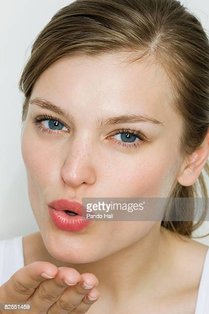 Young woman blowing kiss, portrait
