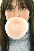 Young woman blowing large bubble with gum, portrait, close-up