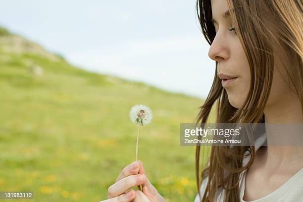 Young woman blowing on dandelion clock