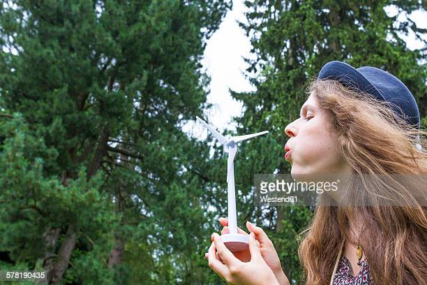 Young woman blowing on model of wind wheel