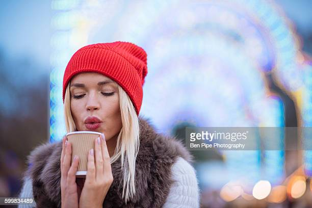 Young woman blowing on mulled wine at Xmas festival, Hyde Park, London, UK
