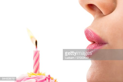 Young woman blowing out birthday candle, close-up