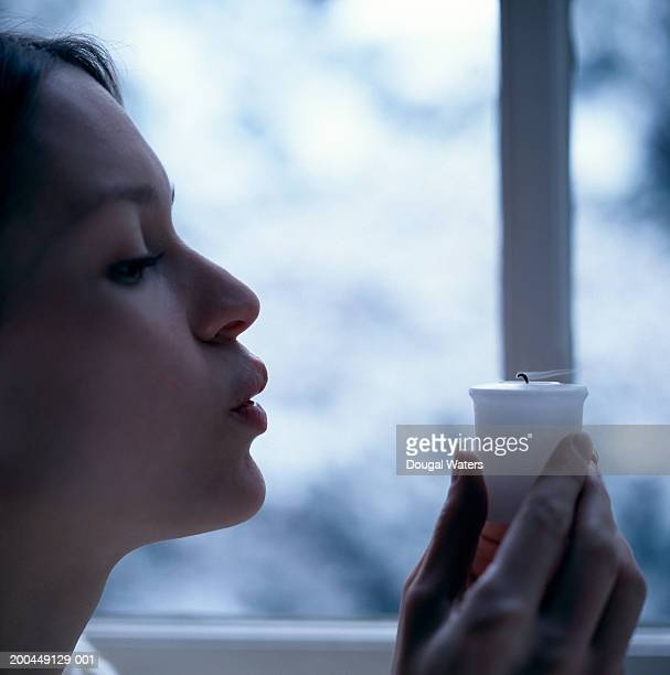 Young woman blowing out candle, close-up, side view