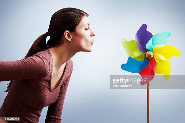 Young woman blowing pin wheel