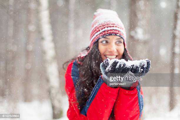 Young woman blowing snow in the snow forest