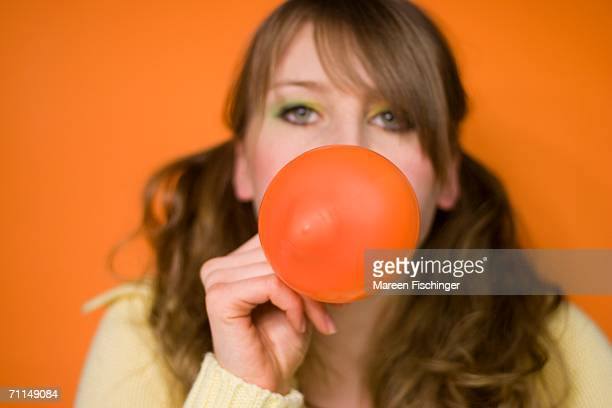 Young woman blowing up balloon, close-up, portrait