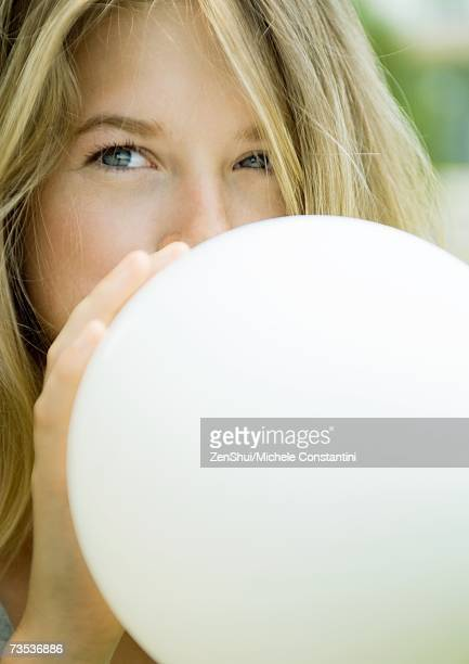 Young woman blowing up balloon