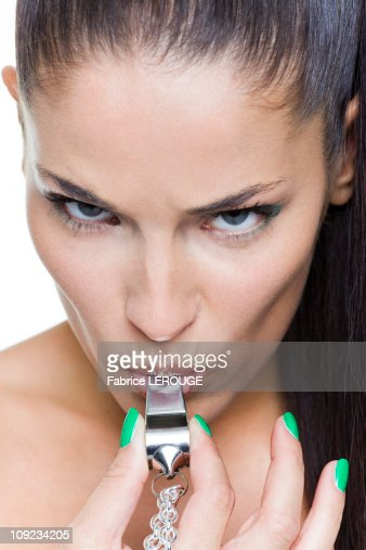 Young woman blowing whistle