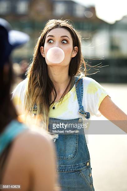 Young woman blows chewing gum bubble