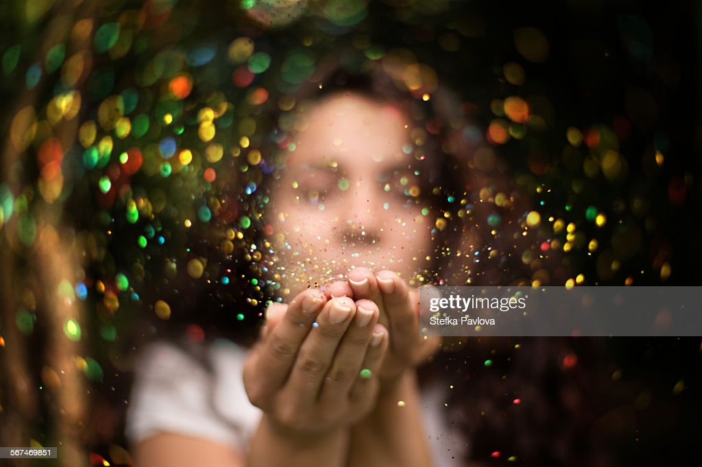 Young woman blows glitter into the air : Photo