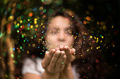 Young woman blows glitter into the air