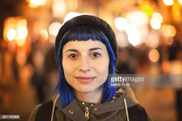 Young woman bluehair walking through citylight