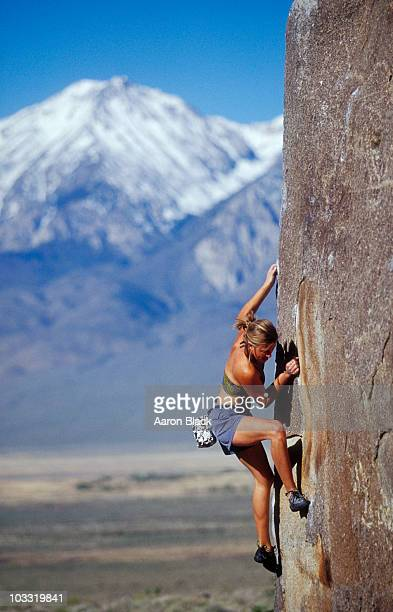 Young woman bouldering in sun with snow capped mountain background.