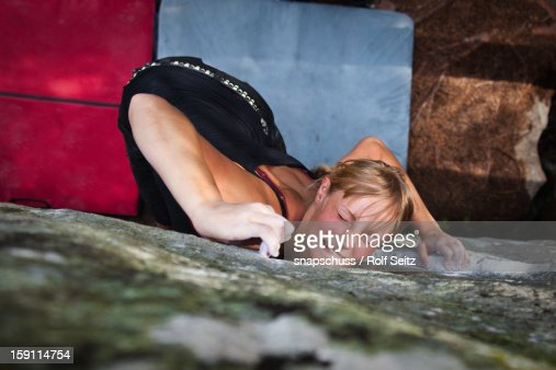 Young woman bouldering intensely : Stock Photo