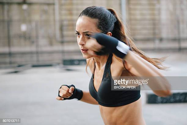 Young woman boxing in urban setting
