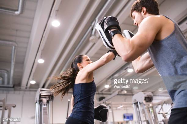 Young woman boxing with her coach