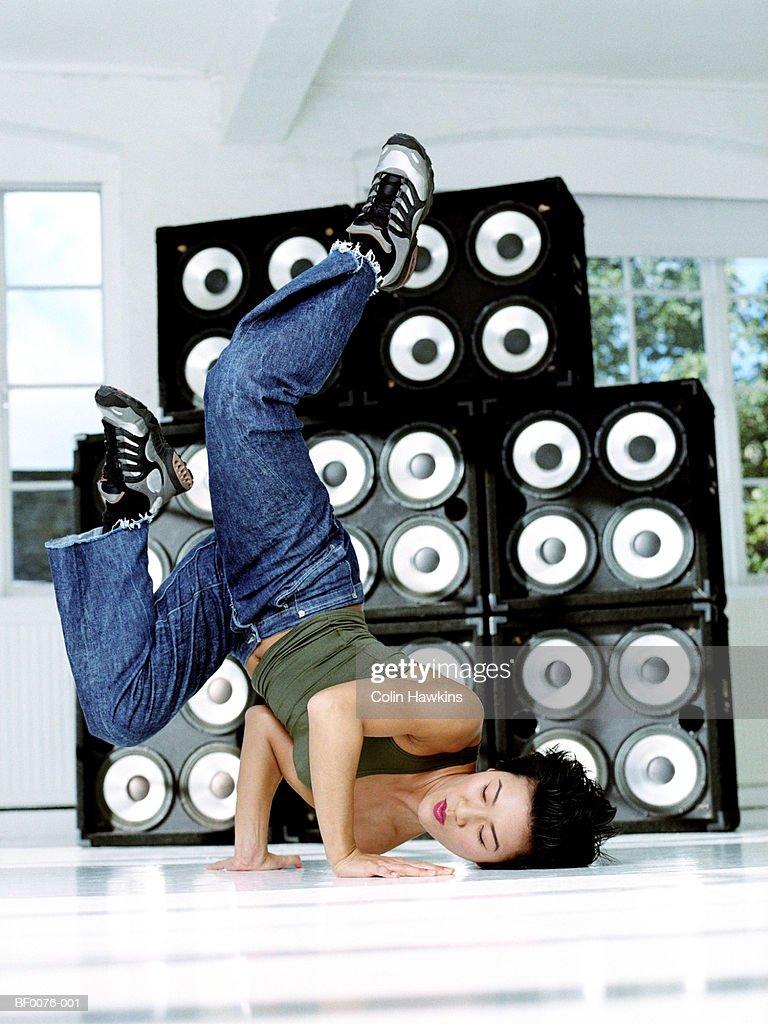 Young woman break-dancing in front of speakers : Stock Photo